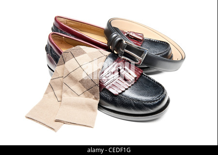 A new pair of slip on dress shoes with tan socks and a black leather belt - Stock Photo