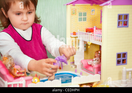 little girl washes a doll in pool of toy house - Stock Photo