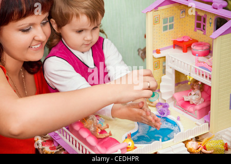 Little Girl and woman washes a doll in pool of toy house - Stock Photo