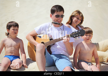 guy in sunglasses plays guitar and  lip accordion  with children and girl sitting on sand - Stock Photo
