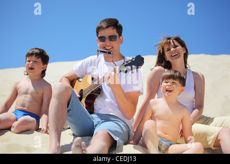 guy in sunglasses plays guitar and  lip accordion  with children and girl singing song sitting on sand - Stock Photo