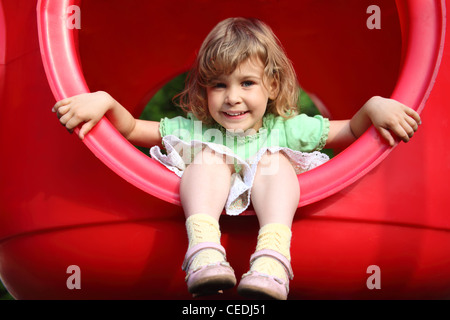 little girl sits in red plastic hole on playground - Stock Photo