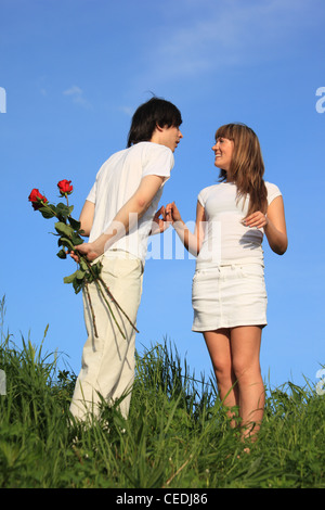young pair stands on a grass,  guy holds behind back bouquet of roses - Stock Photo