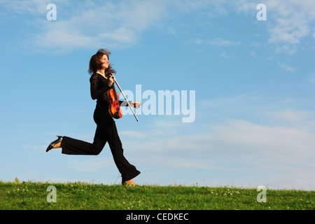 girl with violin runs on grass against  sky, side view - Stock Photo