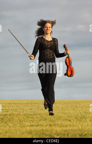 girl with violin runs on grass against  sky, front view - Stock Photo