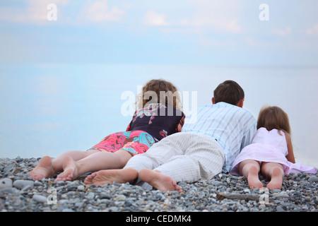 Happy family with little girl lying on stony beach, lying back - Stock Photo