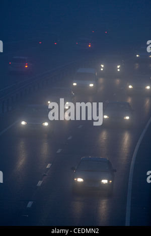 Cars in the fog on road in England at night - Stock Photo