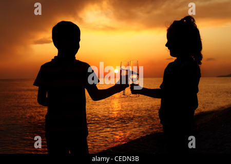 silhouettes of boy and girl with glasses on sea sunset - Stock Photo