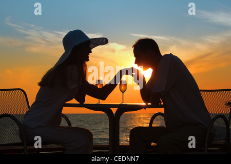 man kisses  hand to  woman on sunset behind  table outside - Stock Photo