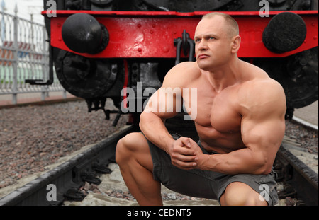 strong shirtless man sits on railroad against locomotive - Stock Photo