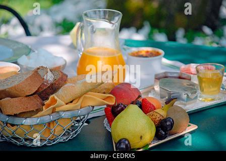 Breakfast ingredients on a table outside, including bread basket, jug of orange juice, fresh fruit - Stock Photo