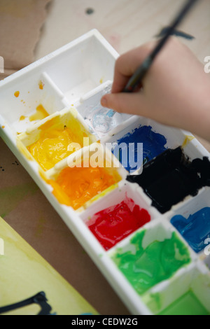 Child holding paintbrush in white paint in palette, close-up - Stock Photo