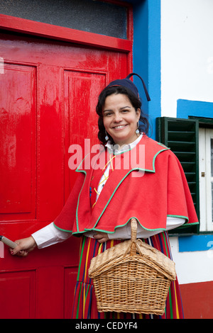 Woman dressed in Traditional costume, red & multi-coloured skirt from Madeira Island outside small thatched triangular - Stock Photo