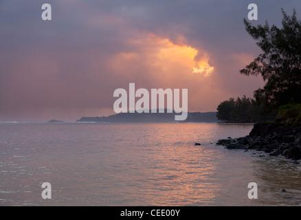 Sunrise on Anini beach with Kilauea lighthouse in the distance - Stock Photo