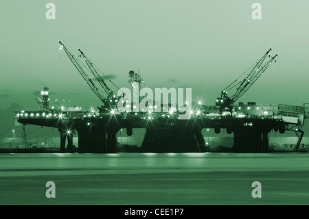 Oil rig at night. Green toned in Photoshop. Could be used to convey Green/clean fuel... - Stock Photo