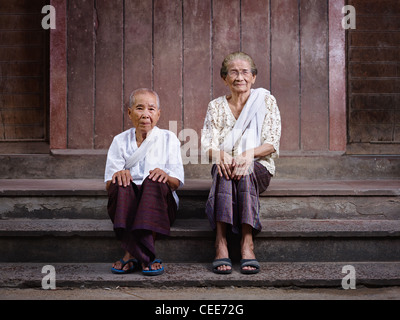 Portrait of two old asian women sitting on steps out of their house and looking at camera - Stock Photo