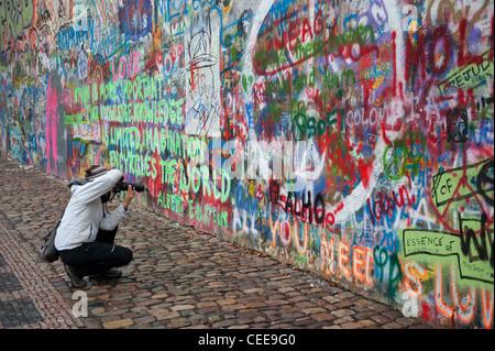 Tourist at the John Lennon tribute wall in the Mala Strana district of Prague, Czech Republic - Stock Photo