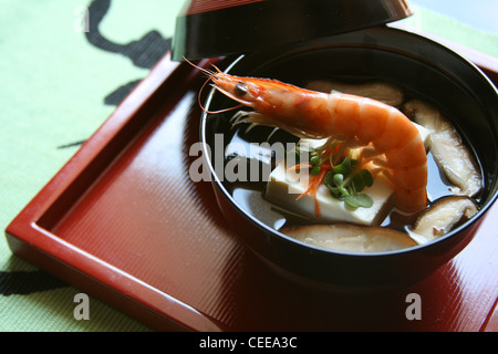 Authentic Japanese cuisine, clear soup broth with shrimp, tofu, shiitake served in traditional bowl and lacquer tray. Kanji