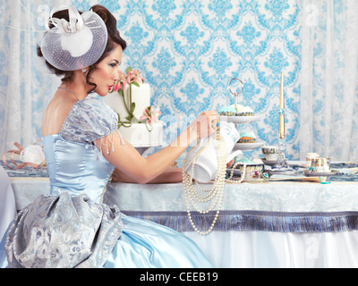 Beautiful asian lady in a luxurious blue dress sitting at a table and pouring tea ina cup. Tea party hostess. - Stock Photo