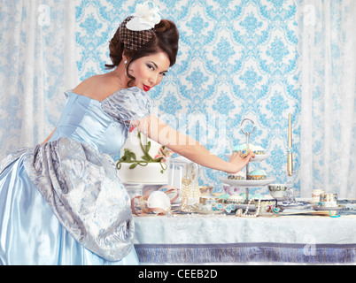 Beautiful asian lady taking a cupcake from a served tea party table indulging in sweets - Stock Photo