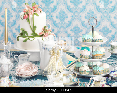 Luxurious tea party still life combining desserts and jewellery - Stock Photo