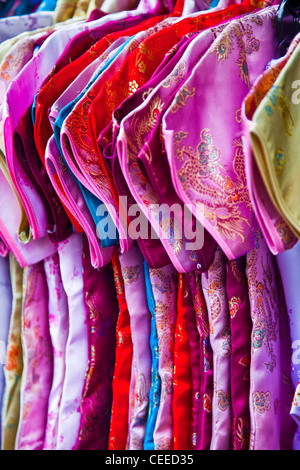 Children's clothing hanging on a rack in Chinatown, Victoria, British Columbia, Canada - Stock Photo