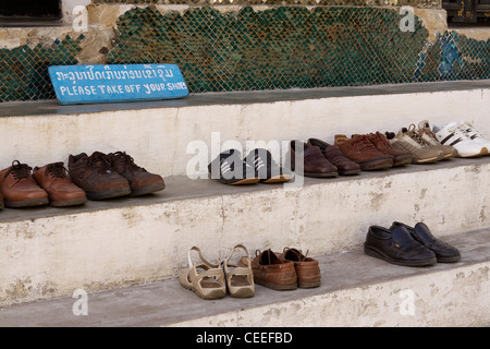Line of shoes removed by visitors outside of Wat Xieng Thong (built in 1560) in Luang Prabang - Stock Photo