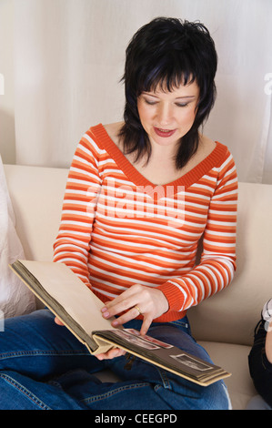Woman looking at old photos in a photo album - Stock Photo
