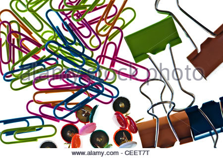 Close-up of coloured paper clips, drawing pins and bulldog clip on white background - Stock Photo