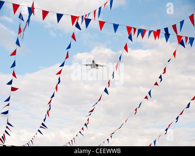 Aircraft Visible through Strings of Bunting in London UK - Stock Photo