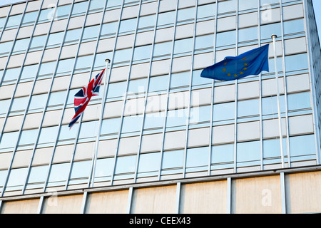 UK flag and EU flag flying together. Union Jack and the European Union flags flying outside offices in Nottingham, - Stock Photo