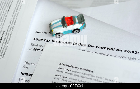 MODEL CAR WITH MOTOR INSURANCE RENEWAL LETTER RE MOTORING INSURANCE COSTS REPAIRS ACCIDENTS RUNNING HOUSEHOLD BILLS - Stock Photo