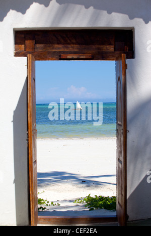 Looking through doorway at dhow, sailing in the sea off the coral reef at Bwejuu, Zanzibar Island, Tanzania - Stock Photo