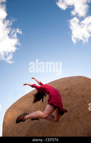 Female dancer in a red dress leaping up into an abstract sky and stone landscape. - Stock Photo