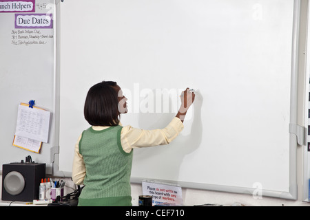 multi ethnic racial diversity racially diverse multicultural multi cultural interracial inter female Teacher writing - Stock Photo