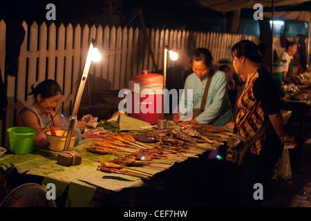 Selling food at night in a street market, Luang Prabang, Laos. - Stock Photo