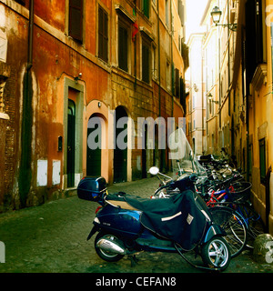 old street in the historic center of Rome with motor scooters and bicycles - Stock Photo