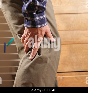 Older man rubbing back of his knee - Stock Photo