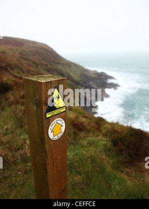 A sign post warning of an unfenced path next to the cliff edge on a public footpath at Treveal Cliff Cornwall England - Stock Photo