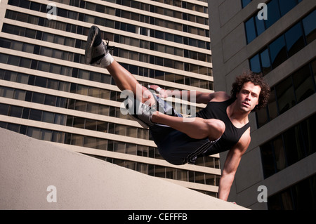 Athlete jumping over urban wall - Stock Photo