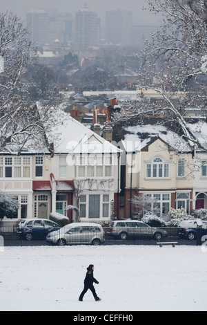 Local resident walks through a snow covered Ruskin Park with background rooftops of residential houses. - Stock Photo