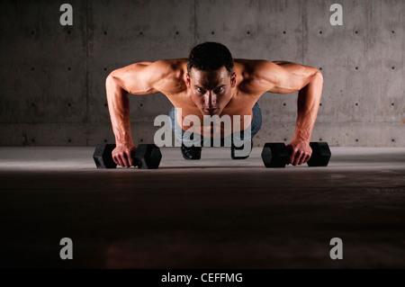 Athlete doing push ups on weights - Stock Photo