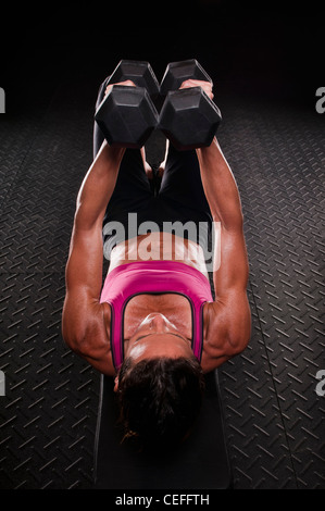 Woman lifting weights in gym - Stock Photo