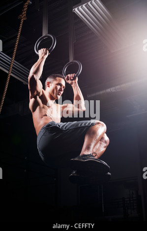 Man using suspended rings in gym - Stock Photo