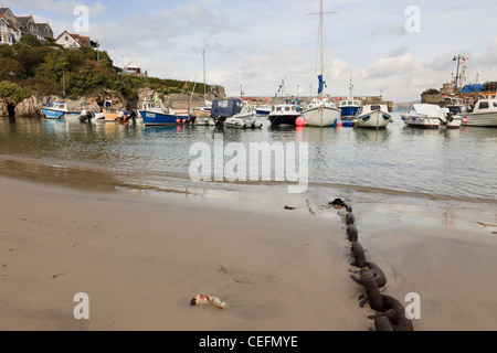 Newquay, Cornwall, England, UK. Chain on the beach and fishing boats moored in the harbour - Stock Photo