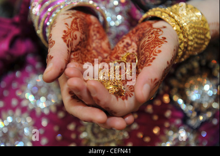 A Pakistani bride holds the wedding rings and jewelery on her wedding day Bradford UK - Stock Photo