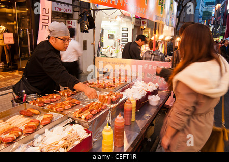 Streets food stalls selling various foods and snacks in the evening in the popular shopping district of Myeongdong - Stock Photo
