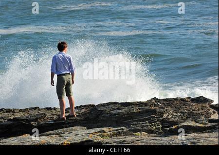 Tourist looking at waves crashing on the rocks at the Pointe Saint-Gildas / Saint Gildas Point, Loire-Atlantique, - Stock Photo