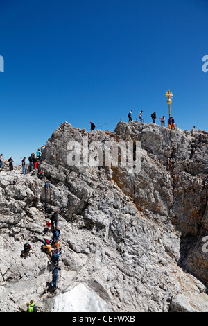 Tourists climbing to the Golden Cross - the highest point in Germany on the summit of Zugspitze at 2,962 m above - Stock Photo