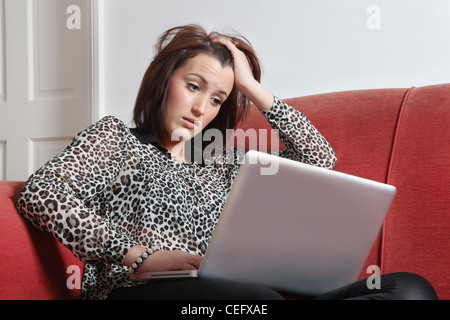 Worried young woman looking at a laptop. - Stock Photo